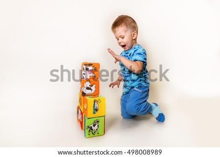 The child plays with cubes. The kid played with bright cubes on a white background.