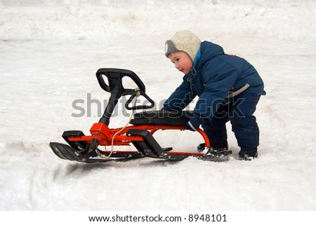 The child pushes sledge on a snow - stock photo