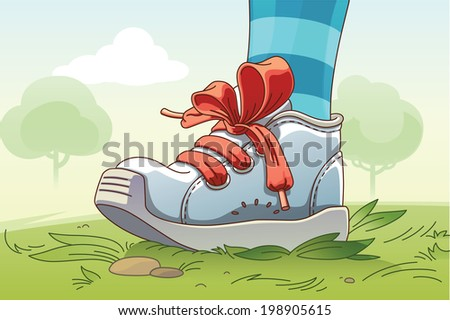 The child's leg wearing the small sneaker with a red lacing is standing on the grass. - stock photo
