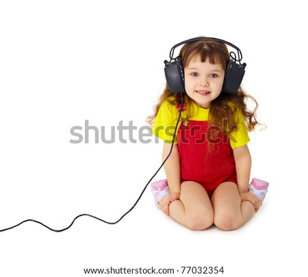The child sits and listens attentively to the music isolated on white background - stock photo