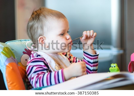 The child sits in a high chair in the kitchen and holding a spoon in his mouth.