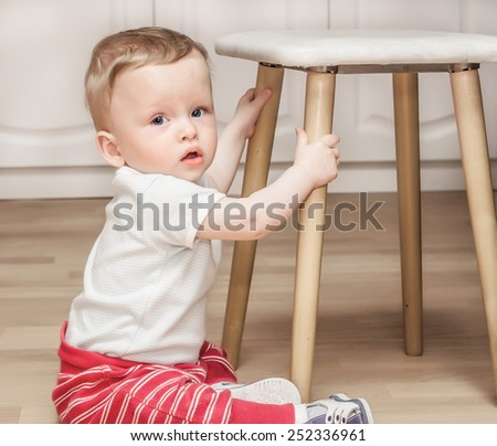 The child sits on a floor near a stool - stock photo