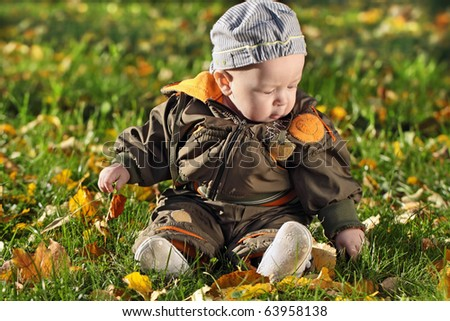 The child sits on a green grass - stock photo