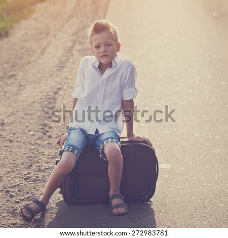 the child sits on a suitcase in the summer sunny day, the traveler,toning image - stock photo