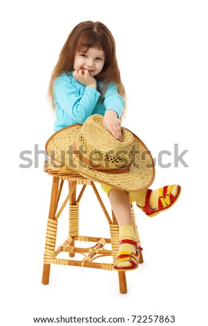 The child sits on an old wooden chair with a straw hat in hand isolated on white background - stock photo