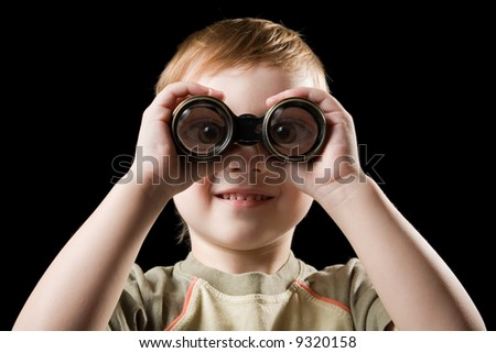 The child watching with binoculars. Isolated on a black background. - stock photo