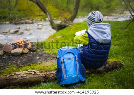 The child who is traveling is looking at a map sitting near a fire in a clearing. - stock photo