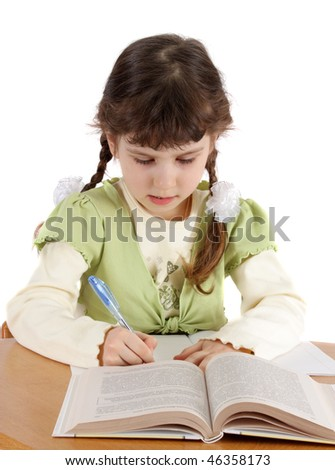 The child writes and reads on a white background, is isolated.