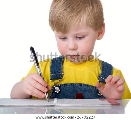The child writes to a notebook sitting on a table