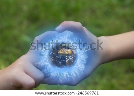 The children are holding a globe in their hands outdoors. Green lawn in the background. Elements of this image furnished by NASA, - stock photo