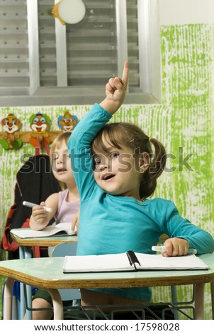 The children are in a school room.  The girl in front is raising her hand to answer a question.  Vertically framed shot. - stock photo