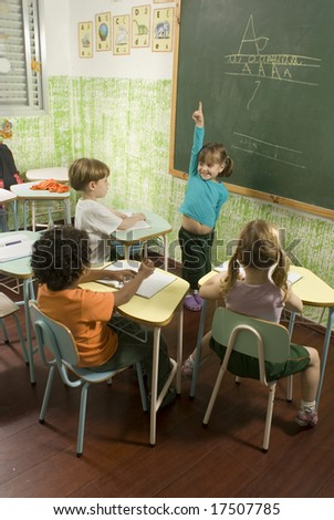 The children are in a school room.  The girl in the blue shirt is showing the classroom something.  Vertically framed shot. - stock photo