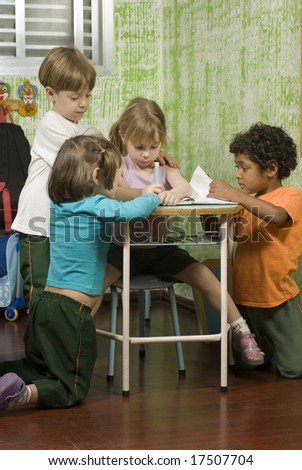 The children are in a school room.  They are looking through the book on the desk.  Vertically framed shot. - stock photo