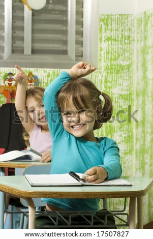 The children are in a school room.  They are raising their hands to answer a question.  Vertically framed shot. - stock photo