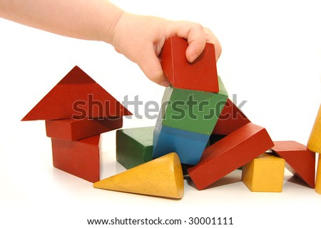 The children hand has destroyed construction from cubes - stock photo