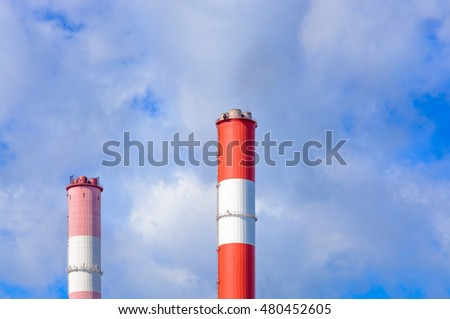 The chimneys against the blue sky with clouds