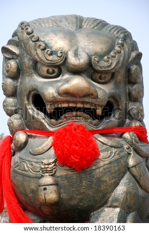 The Chinese bronze lion head sculpture with red silk flower and ribbon.