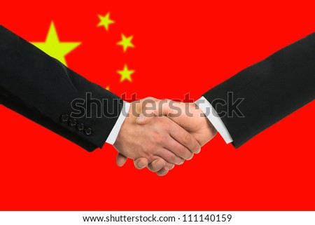 The Chinese flag and business handshake - stock photo
