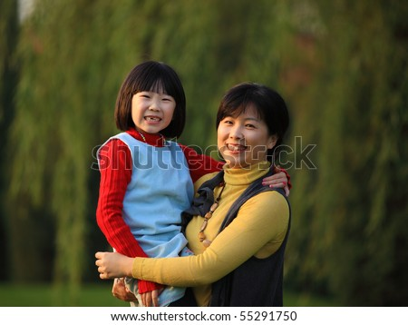 The Chinese mother holding her daughter in autumn - stock photo
