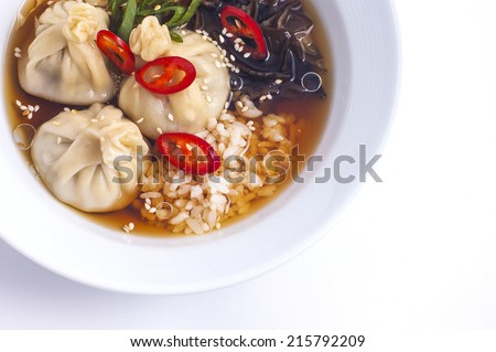 The Chinese pelmeni with a broth and rice the top view - stock photo