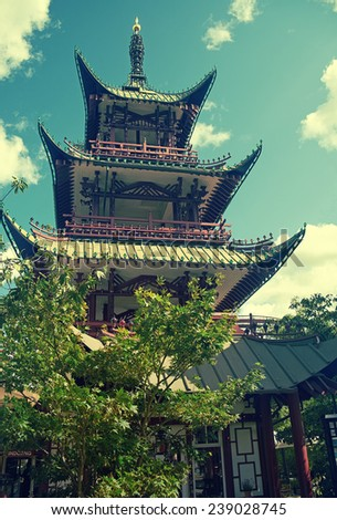 The Chinese Tower in Tivoli Garden in Copenhagen, Denmark. Tivoli Gardens  is a famous amusement park and pleasure garden in Copenhagen.  Tower was built in 1900. Old vintage film colored image - stock photo