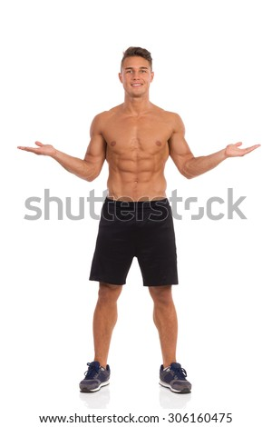 The Choice. Young muscular man in black shorts posing with arms outstretched. Front view. Full length studio shot isolated on white. - stock photo