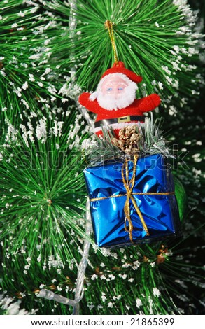 The Christmas decoration of fir tree leaves,Santa Claus doll and gift box.