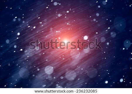 the christmas snowfall in the evening with orange spot light - stock photo