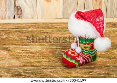The Christmas stocking, covered with Santa's cap, is on a scratched wooden table. Close-up.