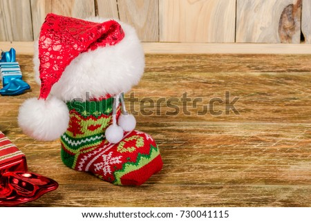 The Christmas stocking, covered with Santa's cap, is on a scratched wooden table. Decorative candies lie nearby. Close-up.