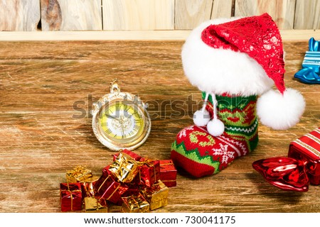 The Christmas stocking, covered with Santa's cap, is on a scratched wooden table. Nearby lie decorative candy,pile of gifts and Christmas clock. Close-up.