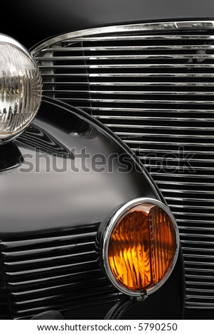 The chrome grill and headlights of an antique classic car.