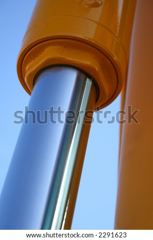 The chromeplated piston of hydraulic system of a dredge on a background of the blue sky, Isolated (look similar images in my portfolio)