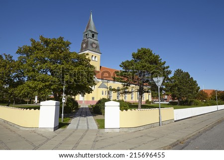 The church at Skagen (Denmark, North Jutland) is built in the typical architectural style and colors with ochraceous walls, a red roof and white joint. - stock photo