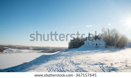 The Church on the hill in the background of a winter landscape