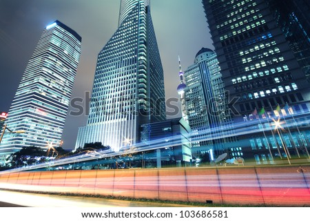 The City background of modern office buildings car night light trails in Shanghai - stock photo
