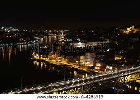 The city bridge lights and their reflections in the Douro river at night in Porto, Portugal.
