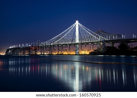 The city lights of San Francisco at twilight with the Bay Bridge on the left. - stock photo