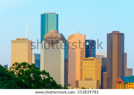 The city of Houston, TX skyline is illuminated by a setting sun