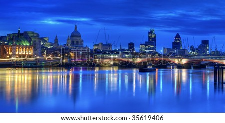The City of London at Dawn. The lights of the city buildings are reflected in the still waters of the River Thames - stock photo