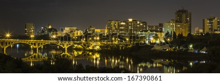 The city of Saskatoon at night along the South Saskatchewan River - stock photo