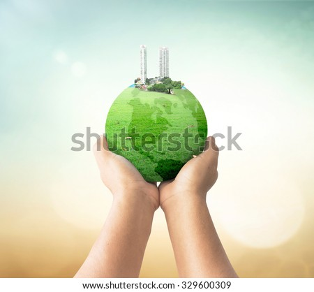 The city on green earth globe of grass in human hands over blurred beautiful nature background. World Environment Day. Ecological city concept. - stock photo
