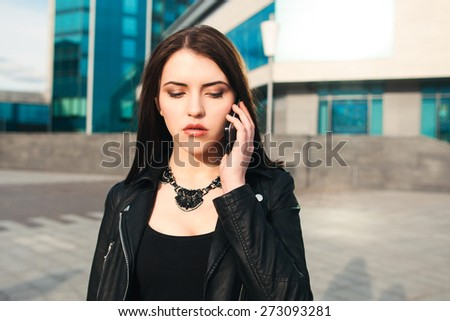 the city sad woman speaks by phone on the street - stock photo
