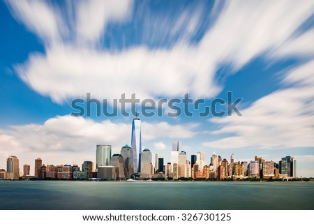 The cityscape of New York as viewed from New Jersey with running clouds on bright blue sky - stock photo