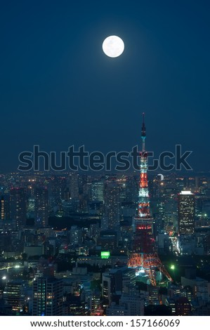 The cityscape of Tokyo at night, beneath a full moon. - stock photo