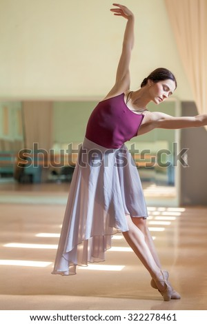 The classic ballet dancer posing at ballet barre on a  rehearsal room background - stock photo