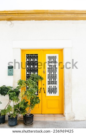 The classical architecture of the Mediterranean (Greece, Italy, Spain, Cyprus, Portugal).  Wooden yellow door on the white buildings and plants. Postal box.  - stock photo