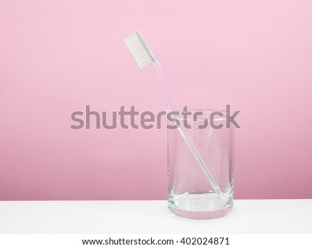 The clear toothbrush with small glass for brushing the teeth. - stock photo