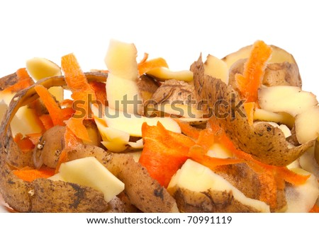 The cleared peel of a potato and carrots on a white background