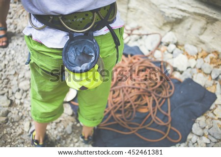 The climber is going to climb the cliff and prepares their gear. - stock photo